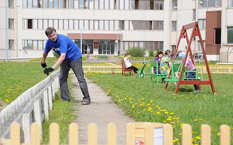 Волонтеры из банка и сотовой компании с членами семей завершают благоустройство детской площадки для больных детей. Фото Кирилла Затрутина